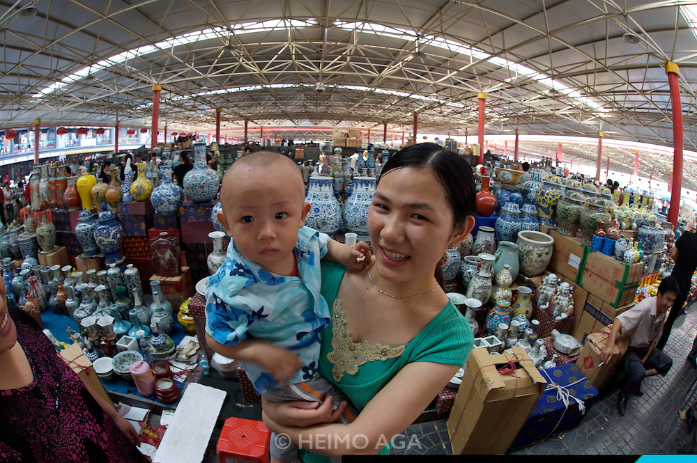 Panjiayuan weekend market. Porcelaine and ceramics. Shop owner with her baby.