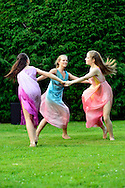 Old Westbury, New York, U.S. 22nd June 2013. Dancers in Lori Belilove &amp; The Isadora Duncan Dance Company, whirl in a circle during a dance of the Three Graces, at the Midsummer Night event at Old Westbury Gardens, throughout the illuminated grounds of the historic Long Island Gold Coast estate.<br />
