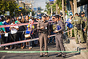 17 JANUARY 2014 - BANGKOK, THAILAND: Officers with the Royal Thai Police investigate the scene of an IED attack on an anti-government protest march. The attackers were not found but officials claim to have found a weapons cache in an abandoned building nearby. Friday was day 5 of the anti-government Shutdown Bangkok protests. The protest, led by the People's Democratic Reform Committee, is calling for the suspension of elections pending political reform in Thailand. There was violence at several sites in Bangkok Friday, including running battles between government opponents and supporters at one site and an IED attack by unknown assailants on anti-government protestors at another site.    PHOTO BY JACK KURTZ