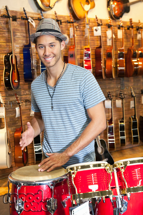 Portrait of a happy young man playing bongo drums with guitars on display in background