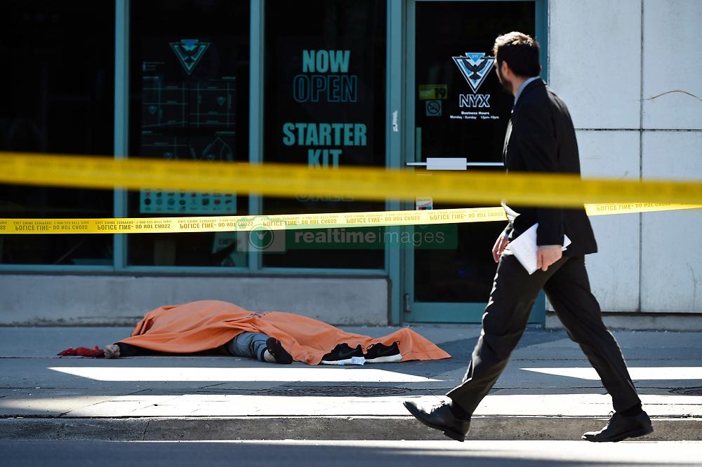a9a1c49b5b52bf A man walks by a covered body in Toronto after a van mounted a sidewalk  crashing.
