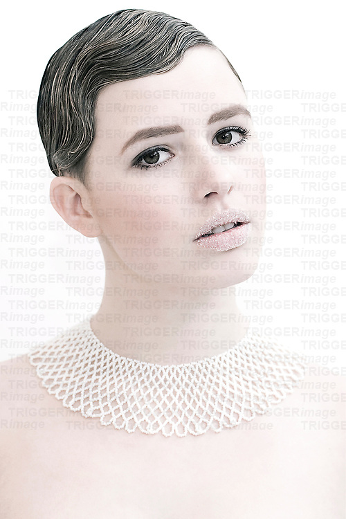 Close up of young woman's face with short hair and brown eyes wearing a delicate lace collar looking at camera