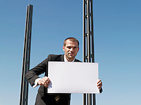 Young man holding sheet of card by concrete pillars