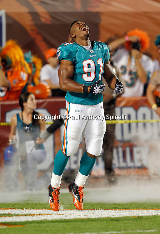 Miami Dolphins linebacker Cameron Wake (91) yells and gets fired up as he enters the field in a cloud of smoke during pregame player introductions at the NFL week 11 football game against the Chicago Bears on Thursday, November 18, 2010 in Miami Gardens, Florida. The Bears won the game 16-0. (©Paul Anthony Spinelli)