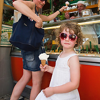 VENICE, ITALY - JUNE 30: Mother and daughter buy an ice cream from Carlo Pistacchi's Gelateria Alaska in Santa Croce on June 30, 2011 in Venice, Italy. Carlo has been making ice-cream using fresh ingredients for more than 25 years and is renowned for experimenting with new flavours, offering his customers classic favourites such as rum and raisin or chocolate as well as some of his more unconventional creations such as asparagus or rocket salad and orange.