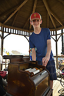 Brooklyn, New York, U.S. - August 9, 2014 - Organ grinder IAN FRASER, 13, of Staten Island, is playing his antique 1881 Celestina Organette, made by the Mechanical Orguinette Company of New York, on the boardwalk at the Fourth Annual History Day at Deno's Wonder Wheel Amusement Park and The Coney Island History Project. Fraser is one of the youngest members of AMICA, the Automatic Musical Instrument Collectors' Association, and COAA, the Carousel Organ Association of America.