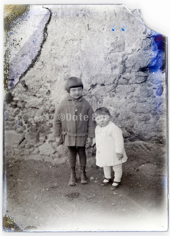 two little children standing by wall on a severely eroding glass plate