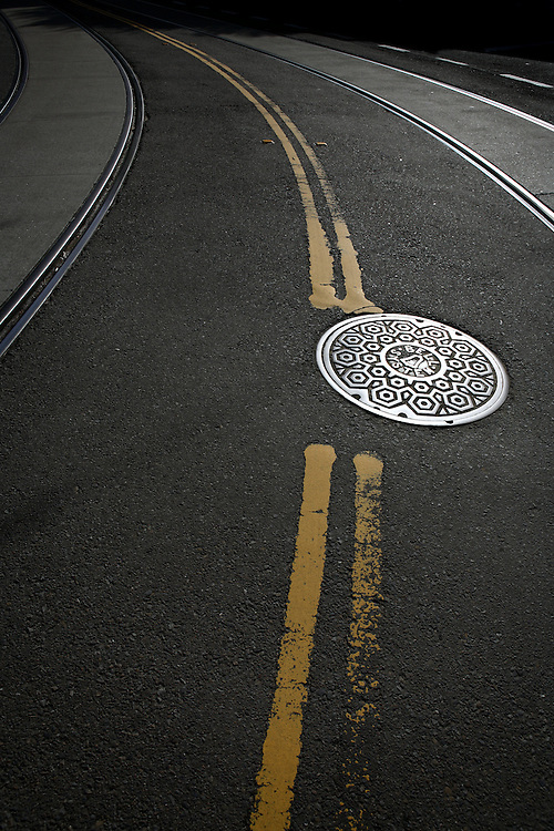 Manhole cover in the middle of a city street.