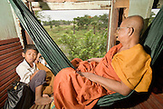 01 JULY 2006 - PHNOM PENH, CAMBODIA: A Buddhist monk sits in the hammock he brought for the Phnom Penh - Battambang passenger train. While much of Cambodia's infrastructure has been rebuilt since the wars which tore the country apart in the late 1980s, the train system is still in disrepair. There is now only one passenger train in the country. It runs from Phnom Penh to the provincial capitol Battambang and it runs only one day a week. It takes 12 hours to complete the 190 mile journey.  Photo by Jack Kurtz / ZUMA Press