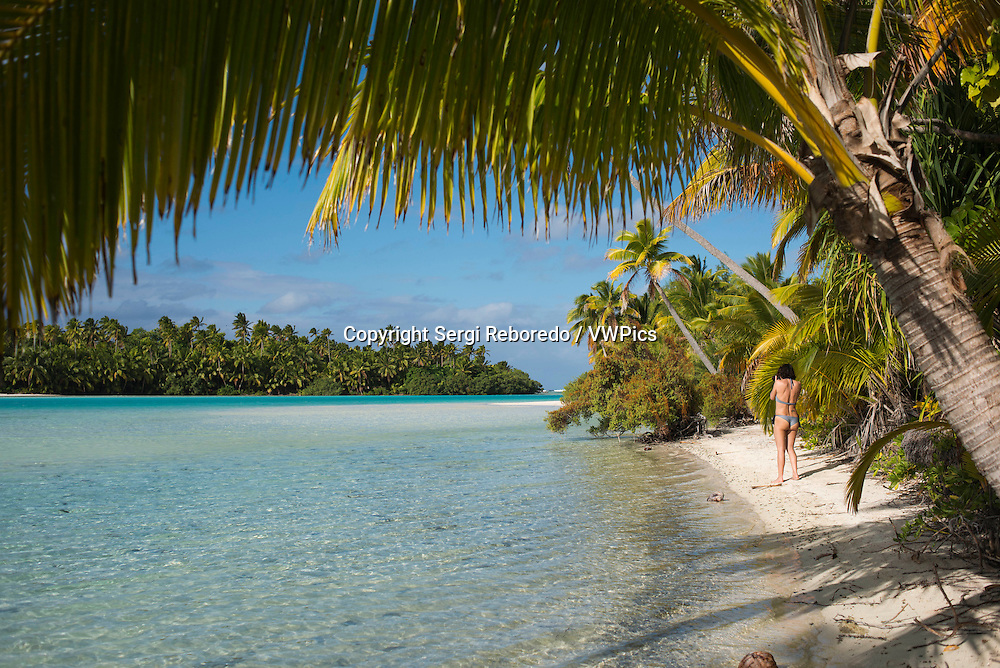 "Aitutaki. Cook Island. Polynesia. South Pacific Ocean. A tourist walks along the edge of the palm-fringed beach in One Foot Island.  Stamp Your Passport: Visit Aitutaki's One Foot Island, where you'll enjoy the incredible blue lagoon and a mouth watering beach barbecue, as well as a chance to receive Aitutaki's trademark One Foot passport stamp.. With a vast, sparkling lagoon rivaling Bora Bora's – but with a fraction of the visitors – Aitutaki just might be the world's most beautifully-remote island. Just a 45-minute flight from the main island of Rarotonga, Aitutaki and its surrounding atolls served as the tropical backdrop for ""Survivor: Cook Islands."" One of 22 islands in the Aitutaki atoll, One Foot Island (or Tapuaetai, ""one footprint"") is both dreamily-exotic and nearly deserted. It's the perfect place to laze on a powder-white beach or float in the knee-high lagoon. While it may look totally deserted, One Foot is home to one top attraction - a small hut containing one of the world's most remote post offices. Don't forget to bring your passport and you'll depart paradise with a footprint-shaped passport stamp to remember it by.  Atiu Island, also known as Enuamanu ('land of the birds') lies 187 kilometres north east of Rarotonga. The third-largest island in the Cooks is over eight million years old. It's also an ecologist's dream and a magnet for the adventurer. On the edge of the island's flat-topped central plateau you'll find Atiu Villas, the island's most developed vacation spot. You'll also find 28 untouched beaches that are almost unvisited – except by those seeking a beautiful, secluded spot. Beautiful Aitutaki. It's believed that the islanders on Aitutaki are descended from Ru, a seafaring warrior who settled there with his four wives. Arriving during a full moon he was captivated by the reflections upon this vast tranquil lagoon and named his landing point O'otu, which means 'full moon'. Today A"