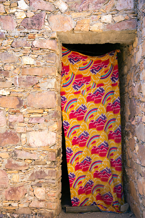 Close up of the exterior of the Ighrem Granary and colorful curtain, Souss Massa Draa, Southern Morocco, 2016-05-26.<br /><br />The Ighrem 'agadir' (singular form of granary in Tamazert Amazigh dialect) is a fortified Berber collective granary.<br /><br />The granary structures (Igoudar - plural form of granary in the Tamazert Amazigh dialect) weren't only built for storing harvests, medicines and possessions; the Amazigh ancestors also constructed them to function as an ancient form of a 'high security bank vault.'<br />The Anti Atlas and the Souss ranges are no strangers to war and conflict. The mountain terrains have been home to many an Amazigh uprising against the central governments during Arab rule and early French Occupation.<br />Although each granary is unique in design, their bee hive like labyrinth interiors of interconnecting tunnels, ladders and passageways holding padlocked chambers collectively resemble a style of architecture that Tolkien might have imagined.<br /><br />Most of the igoudar that remain are thought to date to the 16th and 17th century, although the tradition of building and using collective granaries is estimated to be as old as a millennia.<br /><br />One year of low rainfall can make life very difficult for the mainly self sufficient populous of the Anti Atlas range, who would have been ever more dependent upon the fruits of their harvest during the time of structures development.<br /><br />The crops which are agriculturally viable amid the dramatic climate conditions of the Anti Atlas, such as saffron, almonds, and argan are high in value, with saffron only offering a short annual harvesting window and the stigmas needing optimum storage conditions to preserve life span. <br /><br />Everything from important documents, money and jewellery to the seasons harvest could be stored inside the locked chambers. These well ventilated, shaded rooms built from thick stone walls remain at cool temperatures during high heats. It is possible f