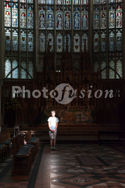 A boy stands in a ray of light inside the Cathedral at Gloucester , Gloucestershire , England , Britain , Uk