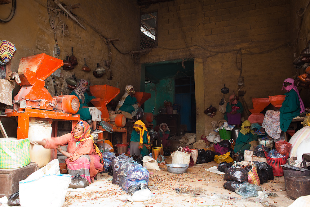 Women working in a small factory in Mekelle that grinds whole dried Berbere peppers into a fine powder for Berbere, a mixture of chili peppers, garlic, ginger, basil, korarima, rue, ajwain or radhuni, nigella, and fenugreek and a key ingredient in Ethiopian cooking.