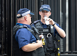 © Licensed to London News Pictures. 26/07/2018. London, UK. An armed police officer on duty at the gates of Downing Street takes a drink of water as London experiences the hottest day of the year so far. Photo credit: Peter Macdiarmid/LNP