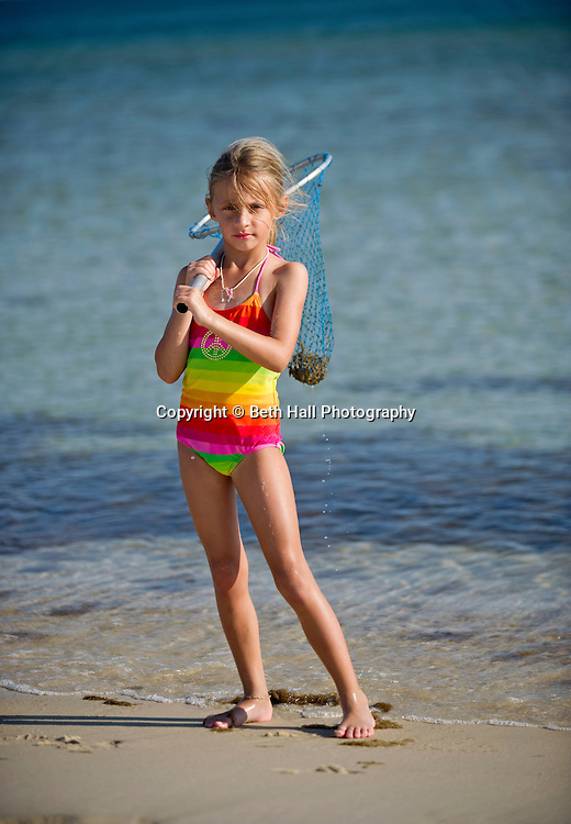 A small girl poses for a portrait on the beach while holding a net containing a crab.