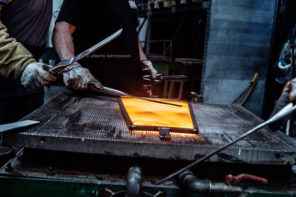 Italy, Resana, Veneto: glass blowers at Nuova Vetreria Resanese, producing for Pulpo designers. Moulding what is going to be part of a glass Lamp