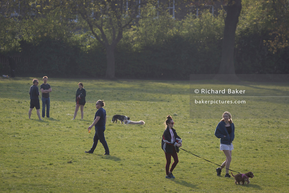 As the Easter Bank Holiday weekend begins and the UK's Coronavirus death toll rises to 7,978 with 65,077 cases testing positive by the end of the UK government's second week of lockdown, Londoners take their daily exercise while practicing social distancing in warm sunshine in Ruskin Park, a south London green space, on 9th April, in London, England.