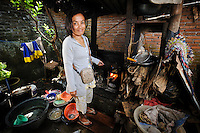 Ibu Buhariah preparing food for sale at the Jongaya leprosy settlement, Makassar, Sulawesi, Indonesia. Ibu Buhariah, 39, is originally from Panglep, Sulawesi.  She discovered she was infected with leprosy at the age of 7 and received treatment at home and at the Daya leprosy hospital before moving to Jongaya when she was 16.  She married in the settlement in 1998 but has no children.  She runs a small business selling prepared food such as fish, tempe and vegetable dishes.  Up until a year ago, Ibu Buhariah would sell from the side of the road outside her house, but she has now bought a mobile kiosk using a loan from Permata.