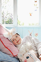 Portrait of young girl (5-6) lying on bed in unicorn costume with toy horse smiling