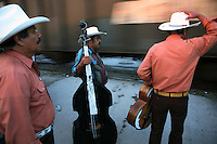 Mariachis wait for a train to pass in Espinazo, Mexico on October 17, 2006. Followers of Nino Fidencio flock to Espinazo, they believe that his spirit can posses other healers, who once possessed speak in a child like voice and perform a variety of medical cures on their followers. His believers, an estimated 20,000, gather in his hometown for a three-day festival twice a year in March and October. (Photo/Scott Dalton)