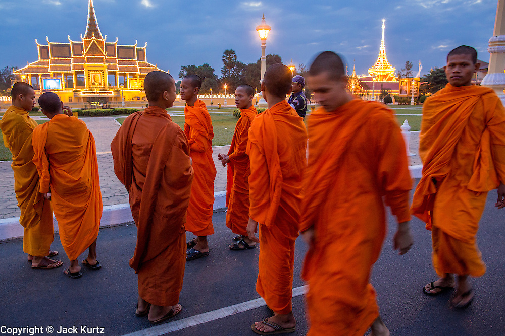 02 FEBRUARY 2013 - PHNOM PENH, CAMBODIA:  Buddhist monks walk along Sisowath Quay, Phnom Penh's riverfront boulevard which is normally choked with cars and motorcycles. The Royal Palace (left) and crematorium for former King Norodom Sihanouk (right) are lit up in the background. Much of Phnom Penh has been shut down to honor former King Norodom Sihanouk, who ruled Cambodia from independence in 1953 until he was overthrown by a military coup in 1970. Only bars, restaurants and hotels that cater to foreign tourists are supposed to be open. The only music being played publicly is classical Khmer music. Sihanouk died in Beijing, China, in October 2012 and will be cremated during a state funeral royal ceremony on Monday, Feb. 4.    PHOTO BY JACK KURTZ