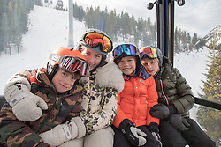 four kids in a gondola going up a ski mountain