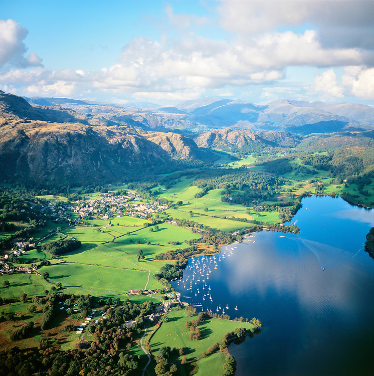 North over Coniston Lake, Coniston village and Yewdale Fells to Helvellyn in the Lake District National Park, Cumbria, England.