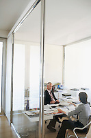 Two businesspeople sitting at desk in office elevated view.