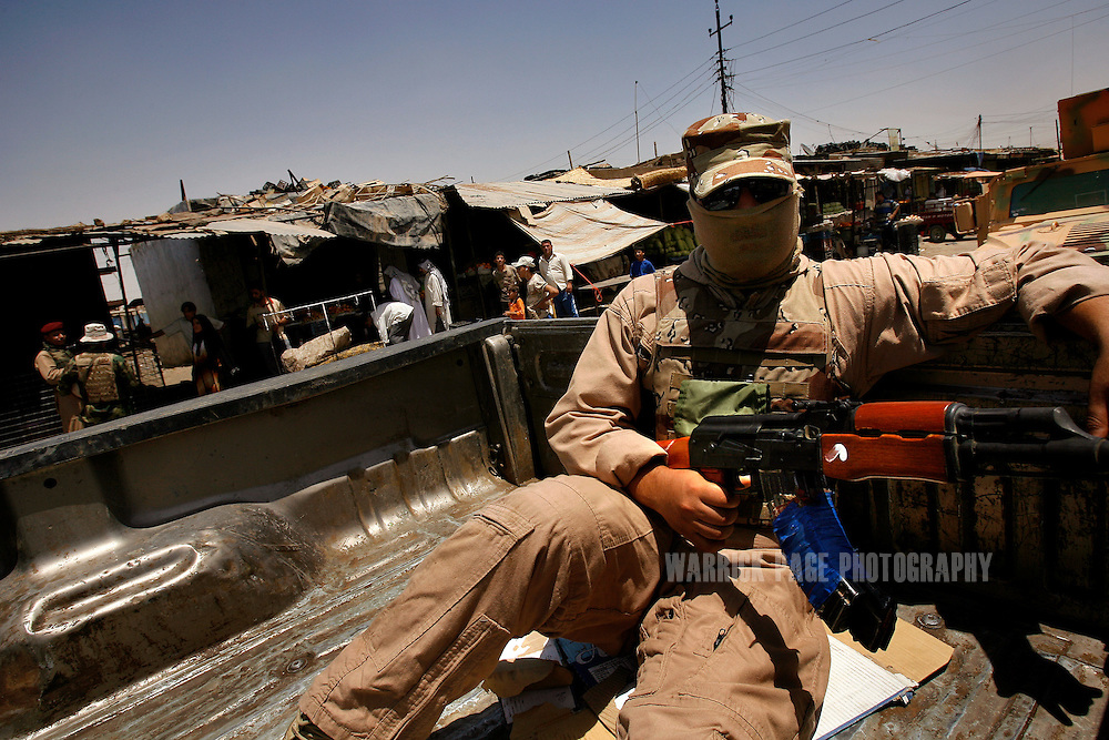 IRAQ, BASRA - JULY 5: An Iraqi soldier mans a machine gun in the back of a pickup truck during a joint patrol with US Marines in the poverty stricken neighborhood of Hayaniyah, July 5, 2008 in Basra, Iraq. When British forces withdrew in 2007, Basra deteriorated into street battles between numerous Shiite militias and criminal gangs. In April 2008, Iraqi prime minister, Nouri al Maliki, sent two Iraqi army divisions to retake control of Basra. While the fighting has ended, unemployment is rife, at about 70 per cent. Since early 2008, Iraq's security situation has improved with oil production increasing, record government surplus and easing sectarian tensions. (Photo by Warrick Page)
