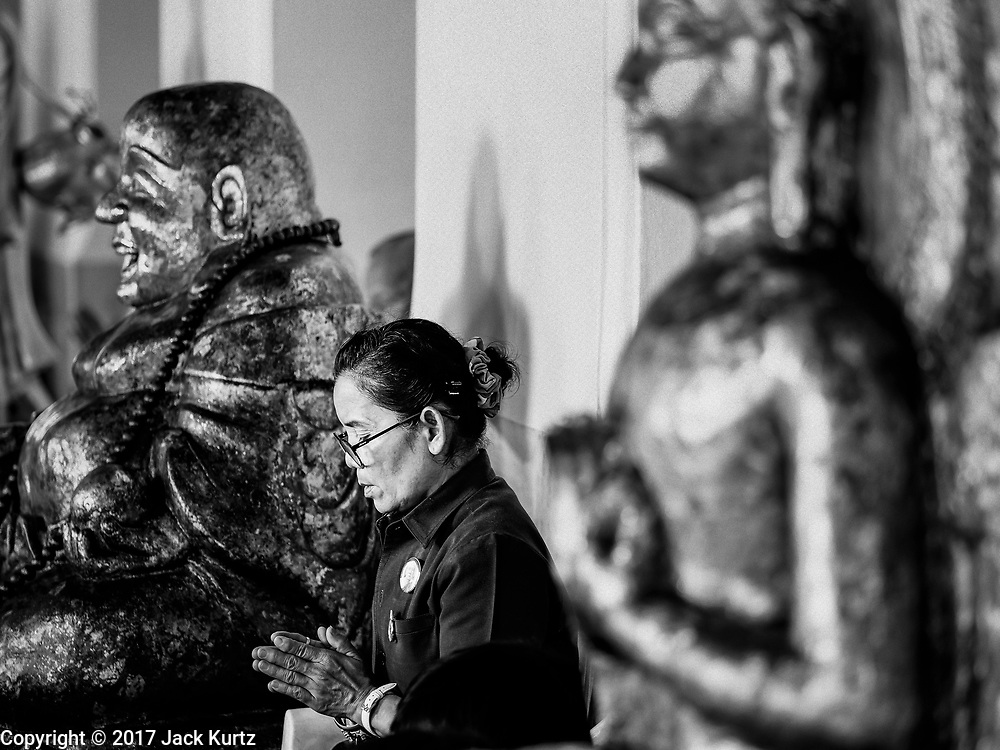 """11 APRIL 2017 - BANGKOK, THAILAND: A woman prays at Wat Chana Songkhram in Bangkok during a Songkran merit making service. Songkran is the traditional Thai Lunar New Year. It is celebrated, under different names, in Thailand, Myanmar, Laos, Cambodia and some parts of Vietnam and China. In most places the holiday is marked by water throwing and water fights and it is sometimes called the """"water festival."""" This year's Songkran celebration in Thailand will be more subdued than usual because Thais are still mourning the October 2016 death of their revered Late King, Bhumibol Adulyadej. Songkran is officially a three day holiday, April 13-15, but is frequently celebrated for a full week. Thais start traveling back to their home provinces over the weekend; busses and trains going out of town have been packed.     PHOTO BY JACK KURTZ"""