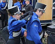 Anamosa Blue Raider Marching Band's Kaurie Davidson (from left), 16, helps Patrick Conley, 16, with his uniform during the 33rd Annual Marion Marching Invitational at Thomas Park Field in Marion on Saturday, September 28, 2013.