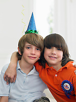 Portrait of two boys (10-12) at birthday party