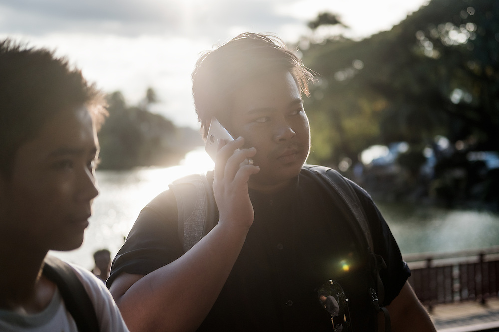 Yangon 20160917<br /> Thar Ko on the phone in a park in central Yangon. <br /> Photo: Vilhelm Stokstad / Kontinent
