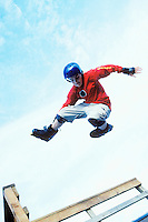 A teenage boy catching some air above a halfpipe in his inline skates.
