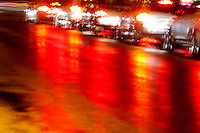 Line of cars at a traffic signal on a rainy night.  All effects created in camera. Photoshop was not used except to adjust exposure and contrast.