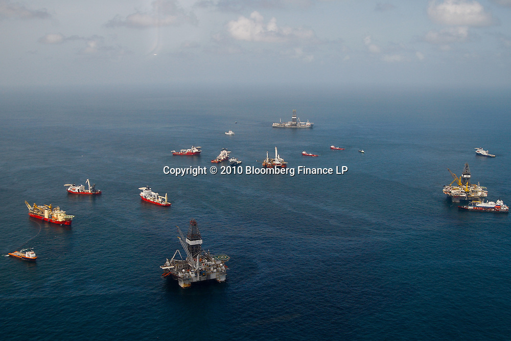 Oil is seen on the surface around vessels and rigs used in containment efforts at the BP Plc MC252 well site in the Gulf of Mexico off the coast of Louisiana, U.S., on Sunday, July 18, 2010. BP Plc said that a pressure test on its damaged Macondo well halted the flow of oil into the Gulf for the first time in three months. The oil spill, the biggest in U.S. history, had been spewing 35,000 to 60,000 barrels of oil a day since the drilling rig exploded on April 20. Photographer: Derick E. Hingle/Bloomberg