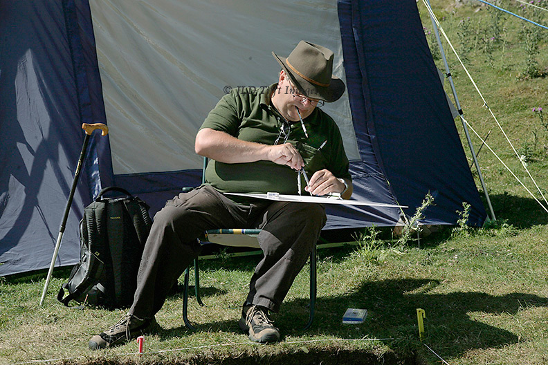 Earthwatch volunteer Robert Sherwin, seated with a drawing board on his knee, makes a careful measured drawing of the archaeological site at Chapel House Wood.
