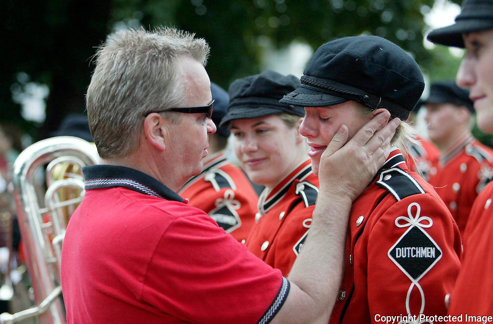 "MOC Floyd-Valley band director Steve Connell, left, comforts senior band member Stacie Oolman after the Pride of the Dutchmen Marching Band's last march in the Orange City Tulip Festival.  Connell said goodbye to 36 seniors, all of whom have been in the band since their freshmen year.  ""I love you all,"" Connell told his seniors before their final march through Orange City's main street.  ""I can't remember my wife's birthday, but if I see any of you in the future, I'll remember your name and what instrument you played.""  The Pride of the Dutchmen Marching Band is one of the most successful competition bands in the state, and have marched in cities all over the country."