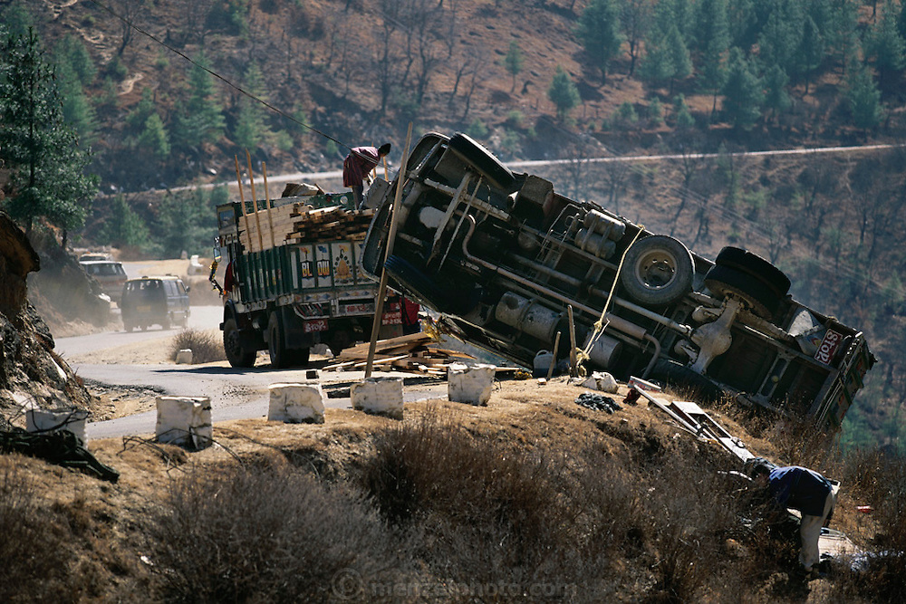 "Truck accident. There is no room for mistakes on the winding narrow one lane ""highway"" that traverses the Himalayan country of Bhutan. It is used most frequently by large trucks hauling goods and people. The driver here was fortunate that the truck didn't plunge down the mountainside from this section of road between the airport town of Paro and the national capital Thimphu. From coverage of revisit to Material World Project family in Bhutan, 2001."