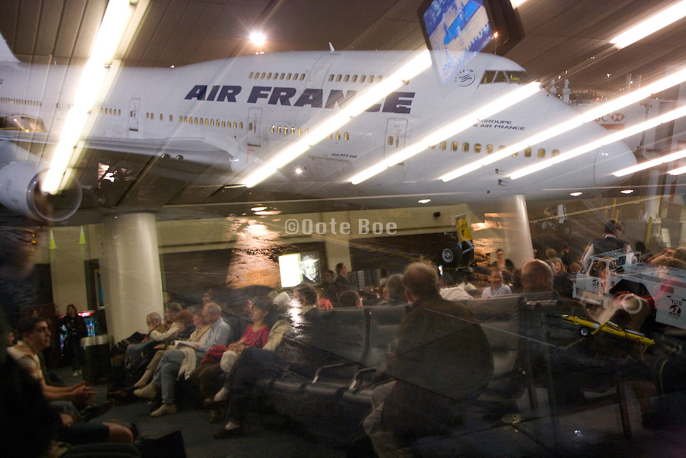 Air France airplane with waiting people reflecting in the window