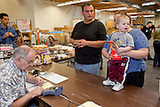Apr. 3, 2009 -- MESA, AZ:  KATRINA HALL, her husband, TIM HALL and their son, ZANE HALL, from Tempe, AZ, pay for the food boxes with Food Stamps at the United Food Bank in Mesa, AZ. Hall said he drives a tourist bus but as the tourism and leisure industry has suffered in the recession his work in disappearing and in March he only work five days. A spokesperson for the United Food Bank in Mesa, AZ, said demand has increased by more than 100 percent in the last year. She said that at this time in 2008, about 175 people a week (the food bank is open one day a week) bought 200 boxes a food but now they were seeing about 350 people per week and they were buying 400-450 boxes of food per week. Each box of food cost $16 and contains enough food for five meals for two people, including meat, fruit and vegetables and starches. In addition to the food boxes, the food bank gives away perishables, like fresh baked goods and produce, that are donated by Phoenix area grocery stores and food producers. She said the number of donations to the food bank have increased as the economy has worsened but each donation is smaller and the gap between donations and what the food bank needs is widening.    Photo by Jack Kurtz / ZUMA Press