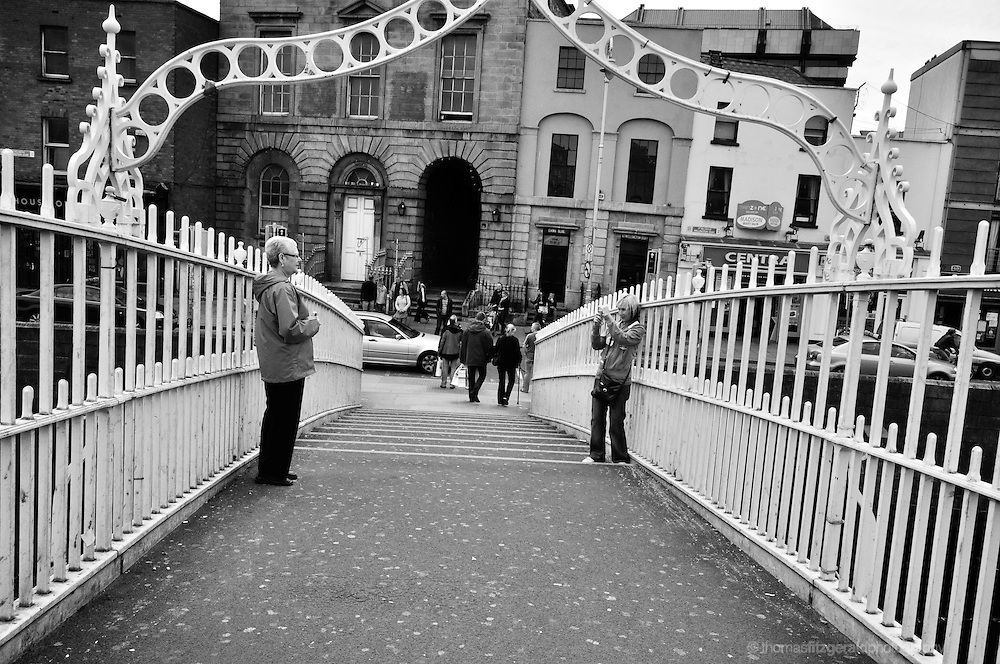 Dublin City, Ireland: On Dublin's Landmark Ha'penny Bridge over the River Liffey, two tourists stop to take pictures.<br />