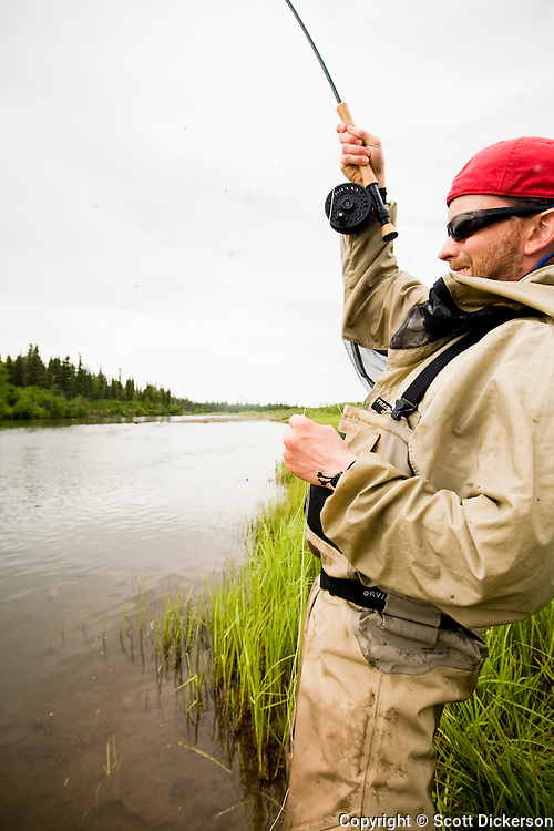 Fly fisherman, Anders Gustafson, fighting a sockeye salmon on the Mulchatna River in Bristol Bay, Alaska.