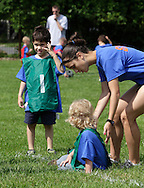 Middletown, New York - A coach helps a child play soccer during a program at the Middletown YMCA on May 28, 2011.