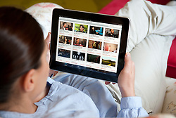 Woman using iPad tablet computer to view movies on Youtube website