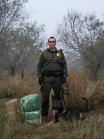 Portrait of a border patrol agent with his drug dog and bags of marijuana they seized along the Rio Grande river, in Hidalgo, TX, on the U.S.-Mexico border, on February 2, 2017 (Photo/Scott Dalton)