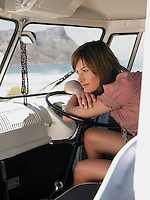Young Woman resting on steering wheel of van view of mountains through window