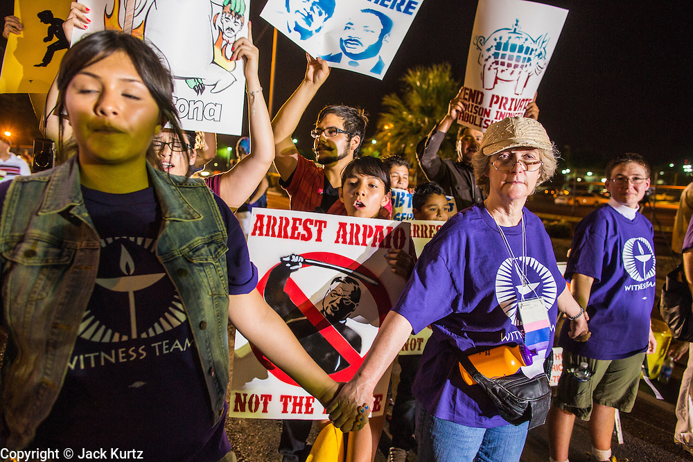 """23 JUNE 2012 - PHOENIX, AZ:  Unitarians keep the crowd back from the jail during a protest against the Maricopa County Jail in Phoenix Saturday. About 2,000 members of the Unitarian Universalist Church, in Phoenix for their national convention, picketed the entrances to the Maricopa County Jail and """"Tent City"""" Saturday night. They were opposed to the treatment of prisoners in the jail, many of whom are not convicted and are awaiting trial, and Maricopa County Sheriff Joe Arpaio's stand on illegal immigration. The protesters carried candles and sang hymns.     PHOTO BY JACK KURTZ"""