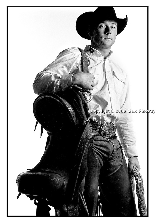 "SHOT 1/23/2003 - Saddle Bronc competitor Cody Martin, 24, of Hatfield, Ark. poses with his saddle after competing in the National Western Stock Show Rodeo Thursday. Martin went to his first rodeo at 13 years old and was so enthralled with the event that he got on a bronc the following evening. Martin drew an unknown bronc and didn't stay on for the required eight seconds that day, therefore he wasn't given a score. Martin was the 2000 PRCA Rookie of the Year. The National Western Stock Show is held every January at the National Western Complex in Denver, Colorado. First held in 1906, it is the world's largest stock show by number of animals and offers the world?s only carload and pen cattle show in the historic Denver Union Stockyards. The stock show is governed by the Western Stock Show Association, a Colorado 501 (c) 3 institution, which produces the annual National Western Stock Show in an effort to forward the association's mission: ""To preserve the western lifestyle by providing a showcase for the agricultural industry through emphasis on education, genetic development, innovative technology and offering the world's largest agricultural marketing opportunities."" Proceeds from the National Western Stock Show go to the National Western Scholarship Trust. The Trust awards 64 scholarships annually to students studying agriculture and medicine to practice in rural areas at colleges and universities in Colorado and Wyoming..(Photo by Marc Piscotty / © 2003)"