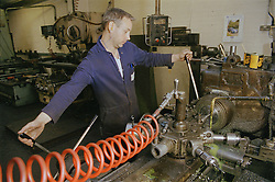 Man centre lathe turning at engineering works,